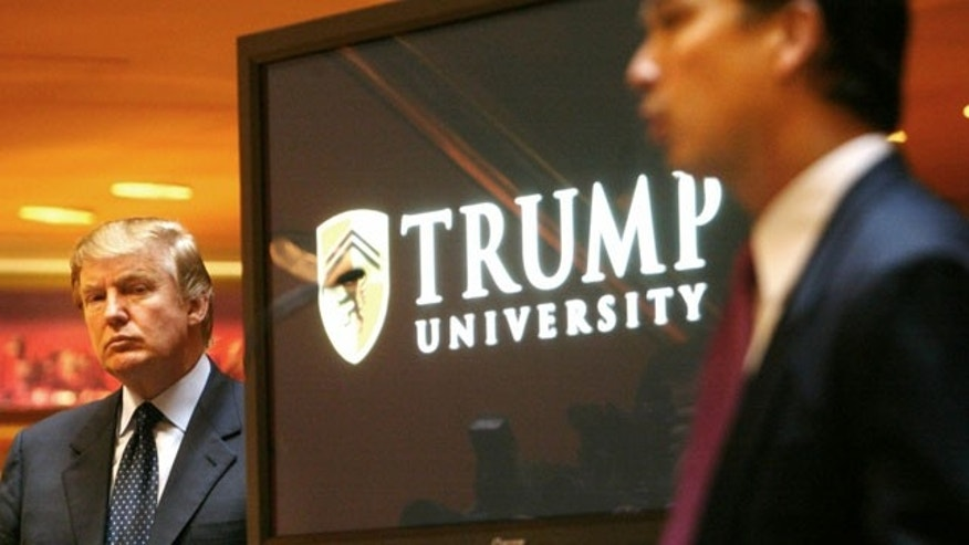 August 25, 2013: Donald Trump, left, listens as Michael Sexton introduces him at a news conference in New York where he announced the establishment of Trump University. (AP Photo)
