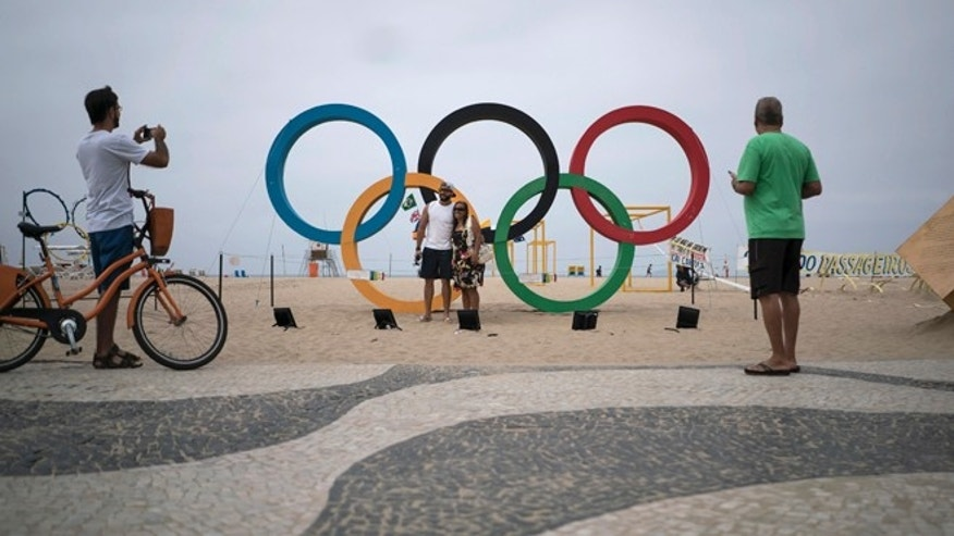 In this July 25, 2016 photo, people take photos by the Olympic rings decorating Copabana Beach in Rio de Janeiro, Brazil. In the city's 2009 Olympic bid document, authorities pledged the games would 'regenerate Rio's magnificent waterways.' A promised billion-dollar investment in cleanup programs was meant to be among the games' most important legacies, but once more, the lofty promises have ended in failure. (AP Photo/Felipe Dana)