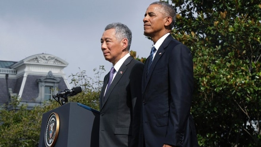 President Barack Obama and Singapore's Prime Minister Lee Hsien Loong stand and watch a state arrival ceremony on the South Lawn of the White House in Washington, Tuesday, Aug. 2, 2016. (AP Photo/Manuel Balce Ceneta)