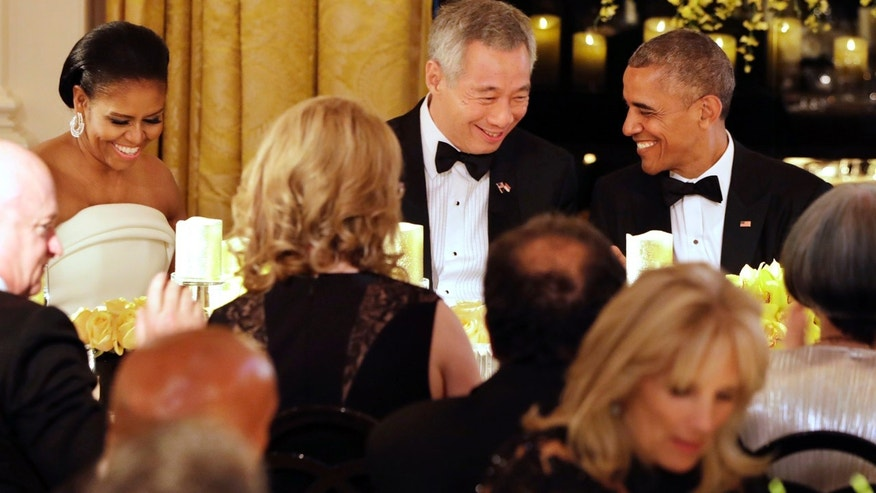 Aug. 2, 2016: President Barack Obama, right, and Singapore's Prime Minister Lee Hsien Loong, talk after toasting each other during a state dinner at the Whie House.