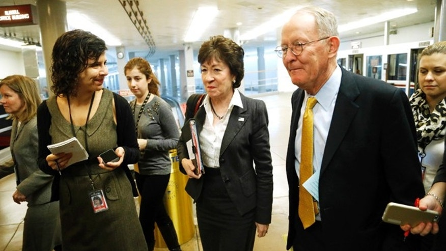 U.S. Senator Susan Collins (R-ME) (C) and Senator Lamar Alexander (R-TN) (R) are greeted reporters as they arrive for the weekly Senate Republican caucus luncheon at the U.S. Capitol in Washington January 13, 2015.