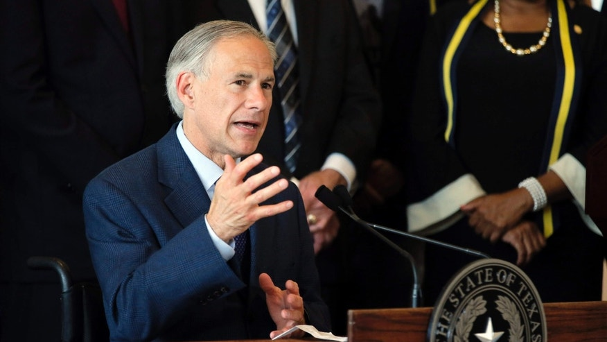 FILE - In this Friday, July 8, 2016 file photo, Texas Gov. Greg Abbott, right, responds to questions about the police shootings during a news conference at City Hall in Dallas.