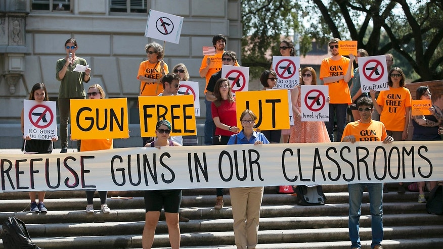 FILE - In this Oct. 1, 2015 file photo in Austin, Texas, protestors gather on the West Mall of the University of Texas campus to oppose a new state law that expands the rights of concealed handgun license holders to carry their weapons on public college campuses and as of Aug. 1, 2016, they can carry in campus buildings.