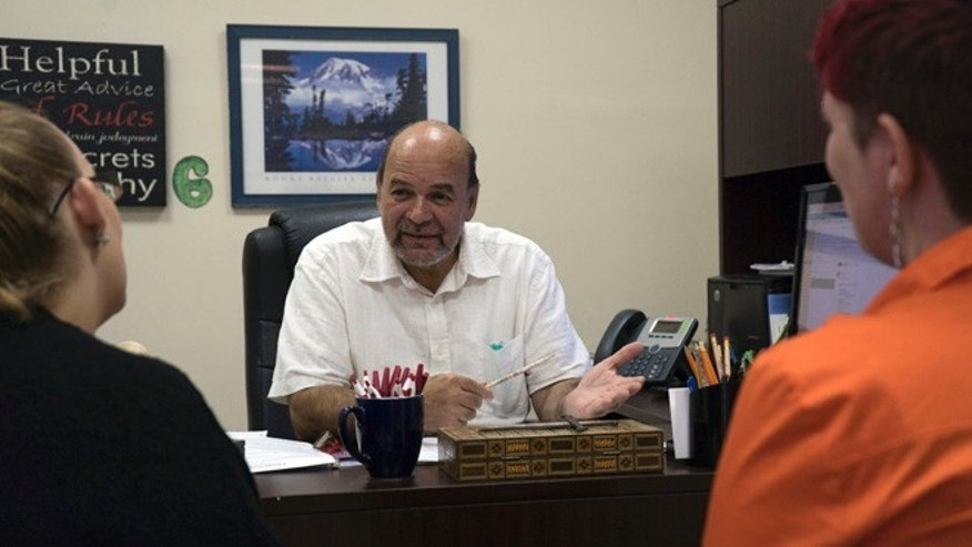 Reverend and Puerto Rican community organization director Robertoluis Lugo Morciglio talks with his colleagues in his office on Friday, Aug.12, 2016. With Puerto Rico's economy in shambles, many are fleeing to the mainland U.S., potentially shifting demographics in some of the country's most critical battleground states. (AP Photo/Dake Kang)