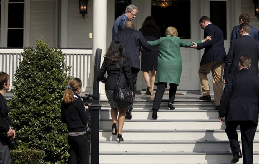 U.S. Democratic presidential candidate Hillary Clinton (in green coat, back to camera) loses her balance briefly as she arrives for a tour of SC STRONG, a home for ex-offenders and substance abusers on the grounds of the former Charleston Navy Yard in North Charleston, South Carolina February 24, 2016. REUTERS/Jonathan Ernst - RTX28EKF