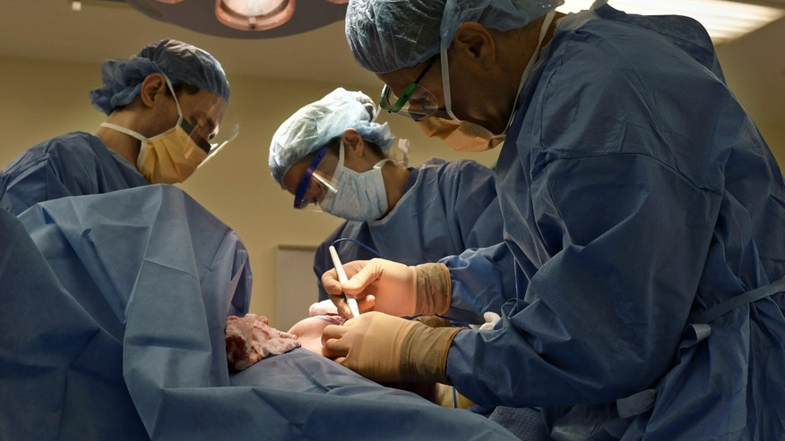 July 15, 2016: Surgeon Dr. Adam Tobias, far right, and Harvard Medical School residents Justin Cohen and Joani Christensen performing a bilateral mastectomy on EJ Silverberg at Beth Israel Deaconess Medical Center.