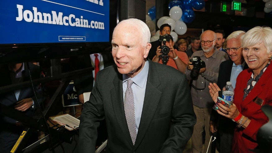 A victorious Sen. John McCain, R-Ariz., walks past supporters as he heads up to the stage to speak after being declared the winner in the Arizona Republican primary Tuesday, Aug. 30, 2016, in Phoenix.