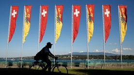 A cyclist passes flags of Switzerland and the Canton of Geneva along the shore of Lake Geneva on a warm and sunny day in Switzerland September 9, 2016.REUTERS/Kevin Lamarque - RTX2OU4M