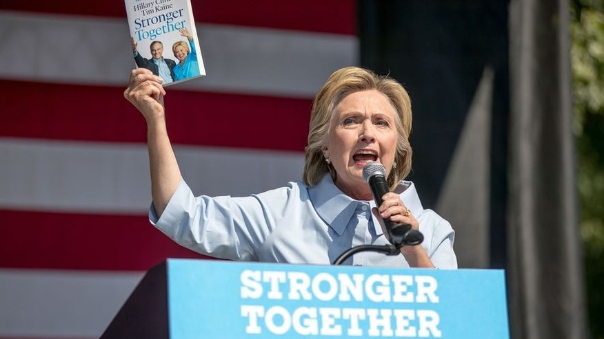 "Sept. 5: Democratic presidential candidate Hillary Clinton holds up a book titled ""Stronger Together"" as she speaks at the 11th Congressional District Labor Day festival at Luke Easter Park in Cleveland, Ohio."