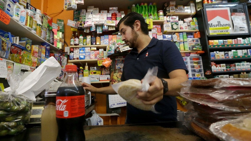 Sept. 21, 2016: Alex Del Rio works behind the counter at his family's market El Ahorro in San Francisco