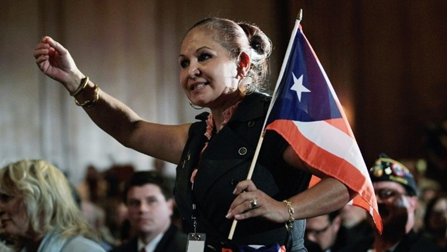 MIAMI, FL - JANUARY 27:  Elizabeth Cuevas-Neunder holds a Puerto Rican flag as she directs a question to Republican presidential candidate and former Speaker of the House Newt Gingrich after he was endorsed by the National Hispanic Leadership Network at the Doral Golf Resort and Spa on January 27, 2012 in Miami, Florida. Gingrich is campaigning ahead of Florida's January 31, primary.  (Photo by Joe Raedle/Getty Images)