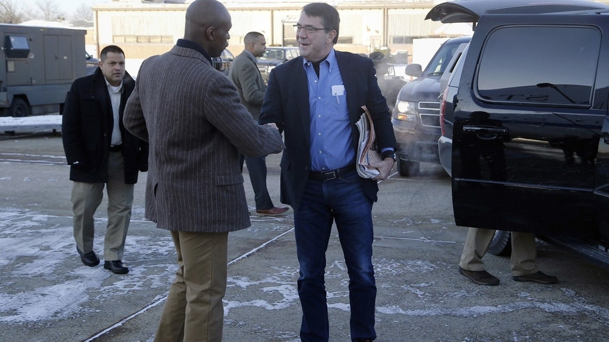 Feb. 20, 2015:  U.S. Secretary of Defense Ash Carter, center, is greeted by Senior Military Assistant U.S. Army Maj. Gen. Ron Lewis as they arrive at Andrews Air Force Base, Md., to travel to Afghanistan.