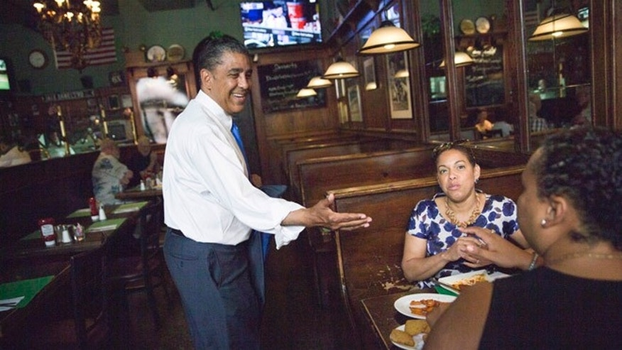 FILE - In this July 6, 2016 file photo, New York Democratic Congressional candidate, New York State Sen. Adriano Espaillat, left, greets diners at a restaurant in the Inwood neighborhood of Manhattan. When the final votes are tallied, count on some trailblazers heading to Congress. New York Espaillat is a near shoo-in in Rep. Charlie Rangel's old district and would be the first person born in the Dominican Republic to get elected to Congress. (AP Photo/Mary Altaffer, File)