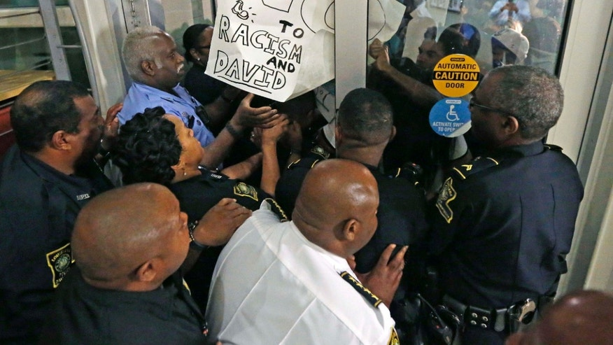 Nov. 2, 2016: Police keep protesters from pushing through a door, before a debate for Louisiana candidates for the U.S. Senate, at Dillard University in New Orleans.