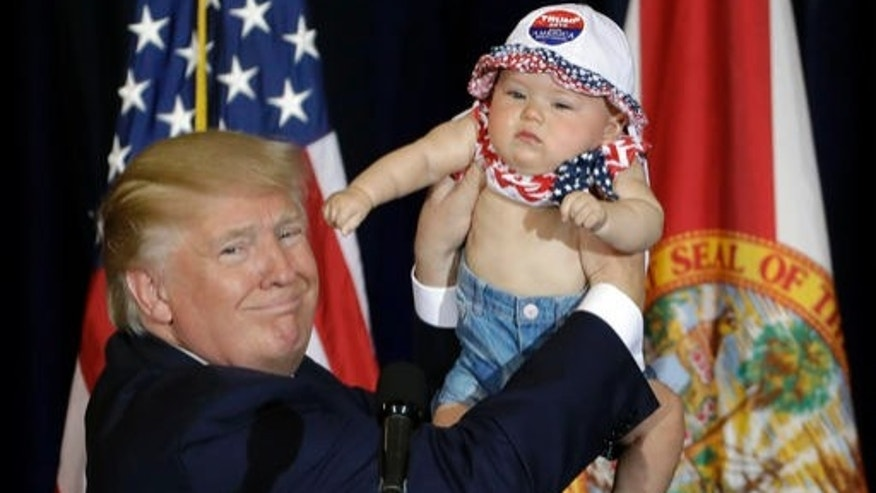 Republican presidential candidate Donald Trump holds up 6-month-old Catalina Larkin, of Largo, Fla., during a campaign rally Saturday, Nov. 5, 2016, in Tampa, Fla. (AP Photo/Chris O'Meara)