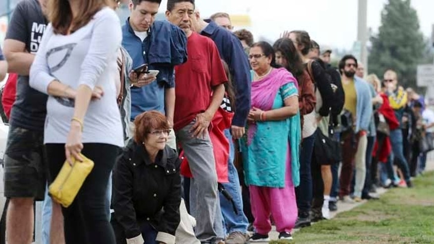 "Diane Sternbach kneels to take a ""back break"" while waiting in line at a weekend early voting polling place at the North Hollywood branch library in Los Angeles Sunday, Oct. 30, 2016. Los Angeles County election officials say some voters waited more than two hours to cast a ballot amid strong interest in early voting. Mike Sanchez, a spokesman for the Los Angeles County Registrar-Recorder, said Sunday that people waited for more than two hours during peak times Saturday at weekend voting centers that opened in and Culver City, Calif. (AP Photo/Reed Saxon)"