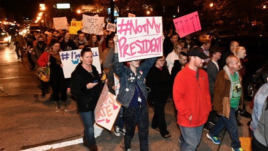 Protesters holds up signs in opposition of Donald Trump's presidential election victory as they march from Jefferson Square Park, Thursday, Nov. 10, 2016 in Louisville Ky. (AP Photo/Timothy D. Easley)
