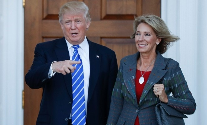 9d5b9df52 FILE - In this Nov. 19, 2016 file photo, President-elect Donald Trump and  Betsy DeVos pose for photographs at Trump National Golf Club Bedminster  clubhouse ...