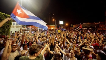 A crowd of Cubans hold hands in solidarity, wave flagsand dance in the street after hearing news that Cuban leader Fidel Castro was ill and ceding power to his younger brother Raul on July 31, 2006 in the Little Havana neighborhood of Miami, Florida.(Photo by Richard Patterson/Getty Images)