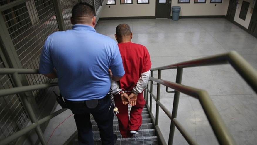 ADELANTO, CA - NOVEMBER 15: A guard escorts an immigrant detainee from his 'segregation cell' back into the general population at the Adelanto Detention Facility on November 15, 2013 in Adelanto, California.  (Photo by John Moore/Getty Images)