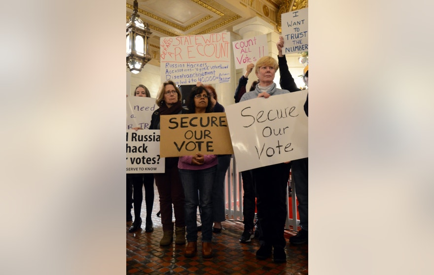 Participants listen to a speaker at a rally at the Pennsylvania Capitol in support of a Green Party-backed quest for a recount of Pennsylvania's Nov. 8 presidential election, Monday, Dec. 5, 2016, in Harrisburg, Pa. (AP Photo/Marc Levy)