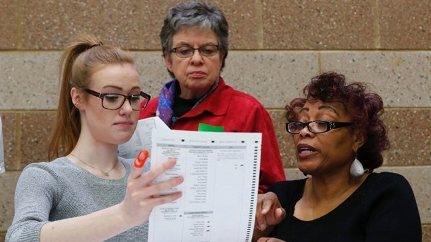 Officials count ballots during a statewide presidential election recount in Waterford Township, Mich., Monday, Dec. 5, 2016. The recount comes at the request of Green Party candidate Jill Stein, who also requested recounts in Pennsylvania and Wisconsin. (AP Photo/Paul Sancya)
