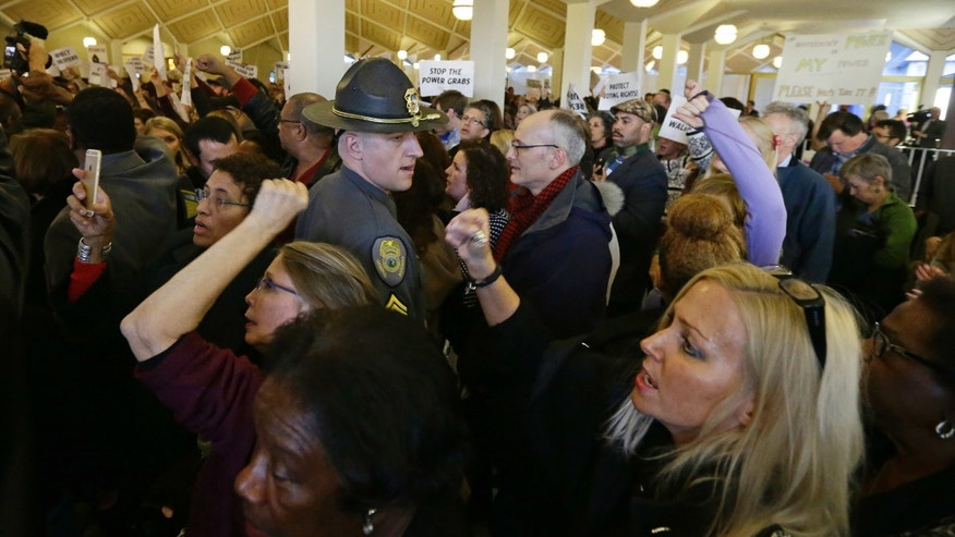 Demonstrators crowd the rotunda outside the House and Senate galleries during a special session at the North Carolina Legislature in Raleigh, N.C., Thursday, Dec. 15, 2016. North Carolina Gov.-elect Roy Cooper said Thursday he's ready to fight in court against Republican legislation moving through the surprise General Assembly session that would undercut his powers as he takes office next month. (AP Photo/Gerry Broome)