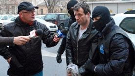 """Jan. 22, 2014: Marcel Lazar Lehel, 40, is escorted by masked policemen in Bucharest, after being arrested in Arad, 337 miles west of Bucharest. Lehel is allegedly the hacker using the nicknames """"Guccifer"""" and """"The Small Fume"""" and is suspected to have broken into several e-mail accounts of various politicians and celebrities and the head of Romania's Intelligence Service George Maior."""