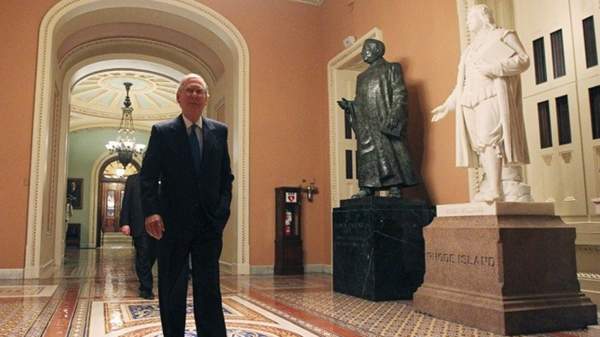Sept. 30, 2013: U.S. Senate Minority Leader Mitch McConnell (R-KY) walks past statues of former U.S. Senators Patrick Anthony McCarran (2nd R) and Roger Williams (R) as he departs the Senate chamber.