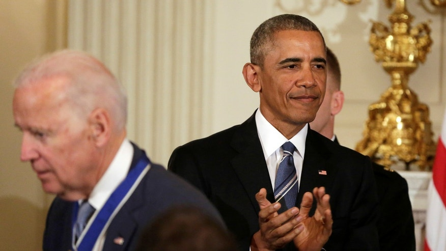 U.S. President Barack Obama (R) applauds after presenting the Presidential Medal of Freedom to Vice President Joe Biden in the State Dining Room of the White House in Washington, U.S., January 12, 2017. REUTERS/Yuri Gripas - RTX2YQ15