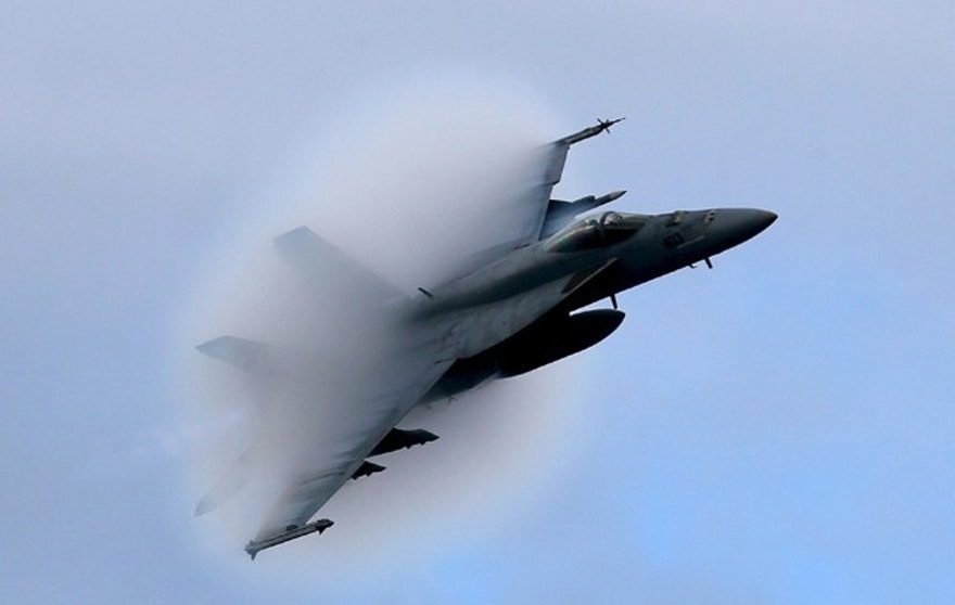 A F18 Super Hornet creates a vapor cone as it flies at a transonic speed while doing a flyby of the USS Eisenhower off the coast of Virginia, in the Atlantic Ocean, December 10, 2015. Carter visited the carrier with Indian Defence Minister Manohar Parrikar to demonstrate U.S. Navy aircraft carrier flight operations. REUTERS/Mark Wilson/Pool - RTX1Y6HJ