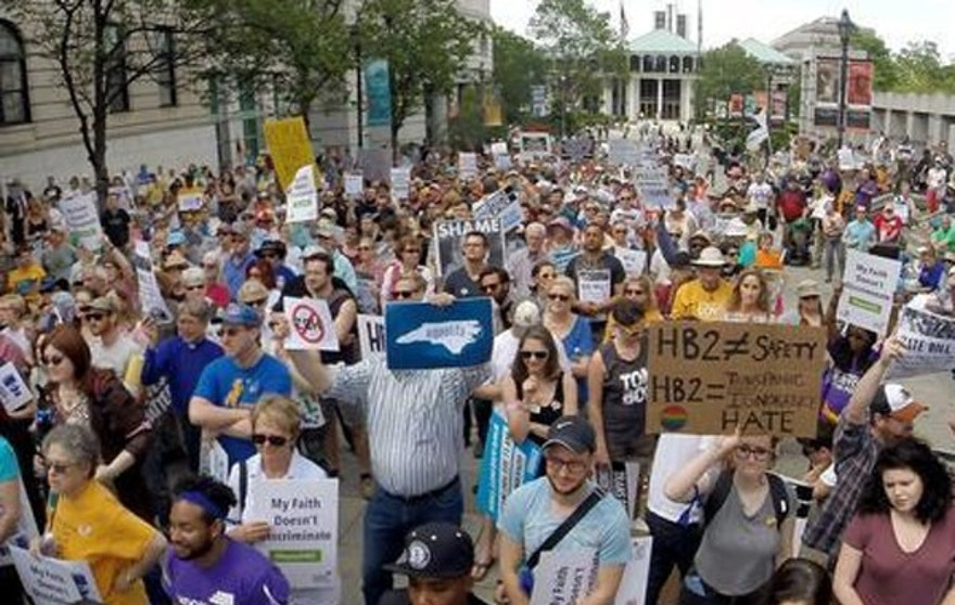 FILE - In this April 25, 2016 file photo, protesters rally against House Bill 2 in Raleigh, N.C., which would require transgender people to use restrooms in many public buildings that match their original gender. Because of the bill, several major sports organizations shifted events away from North Carolina and businesses such as PayPal decided not to expand in the state. In November, Republican Pat McCrory, who signed and defended the bill, became the only incumbent governor to lose in the general election. (Chuck Liddy/The News & Observer via AP)