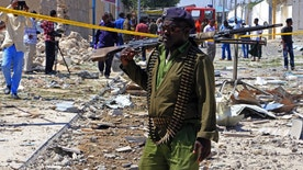 FILE - In this Jan. 2, 2017, file photo, a Somali soldier patrols the area of a suicide car bomb attack in Mogadishu, Somalia. The Pentagon wants to expand the military's ability to battle al-Qaida-linked militants in Somalia, potentially putting U.S. forces closer to the fight against a stubborn extremist group that has plotted attacks against America, senior U.S. officials said. (AP Photo/Farah Abdi Warsameh, File)