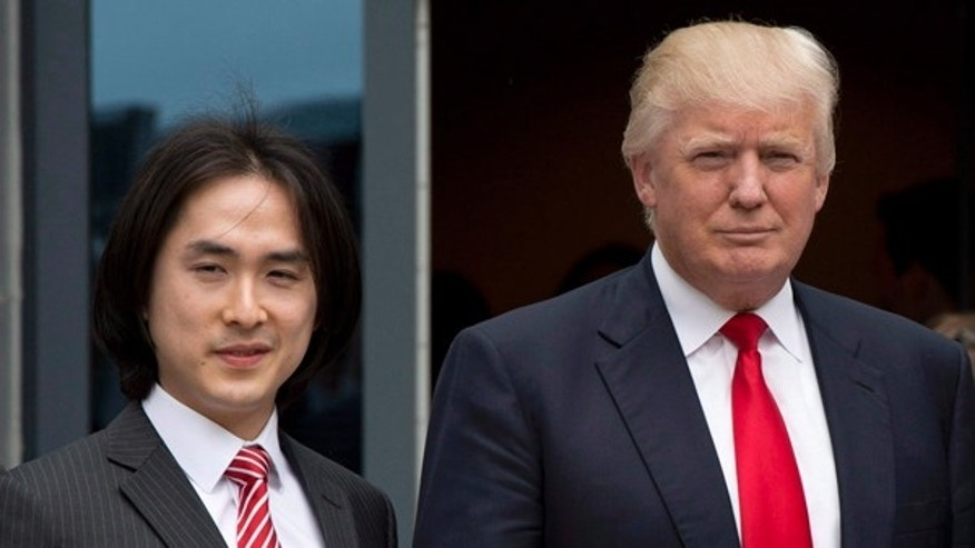 Donald Trump poses with Tiah Joo Kim, left, CEO and president of Holborn Group, on June 19, 2013.