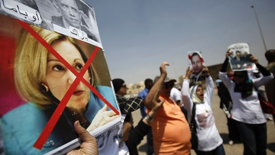 A supporter of Egypt's former President Hosni Mubarak holds a defaced picture of former U.S. ambassador to Egypt Anne Patterson as others shout slogans against members of the Muslim Brotherhood and supporters of ousted Egyptian President Mohamed Morsi, outside a police academy before Mubarak's trial in Cairo July 6, 2013.