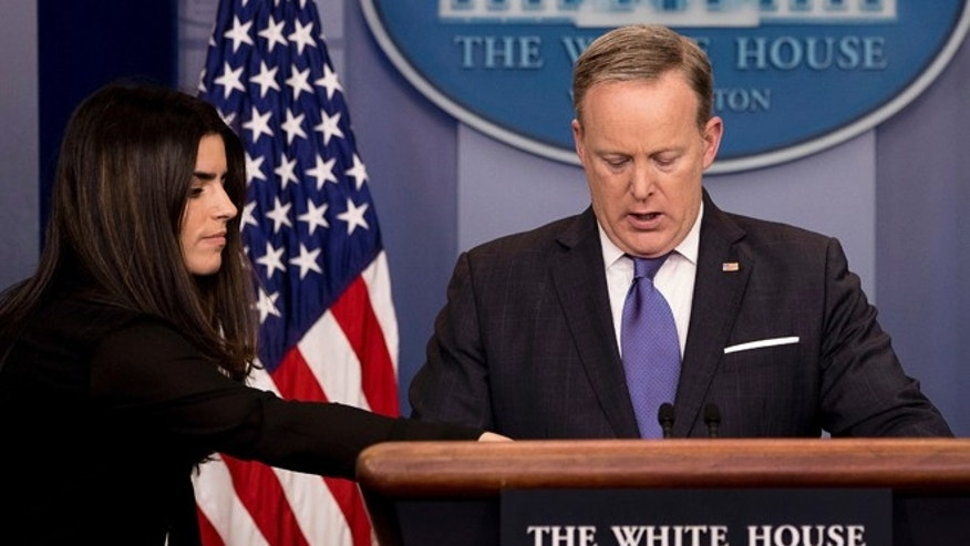 March 13, 2017: Giovanna Coia, with the White House press office, left, hands a note to White House press secretary Sean Spicer as he meets with the media during the daily press briefing at the White House in Washington.