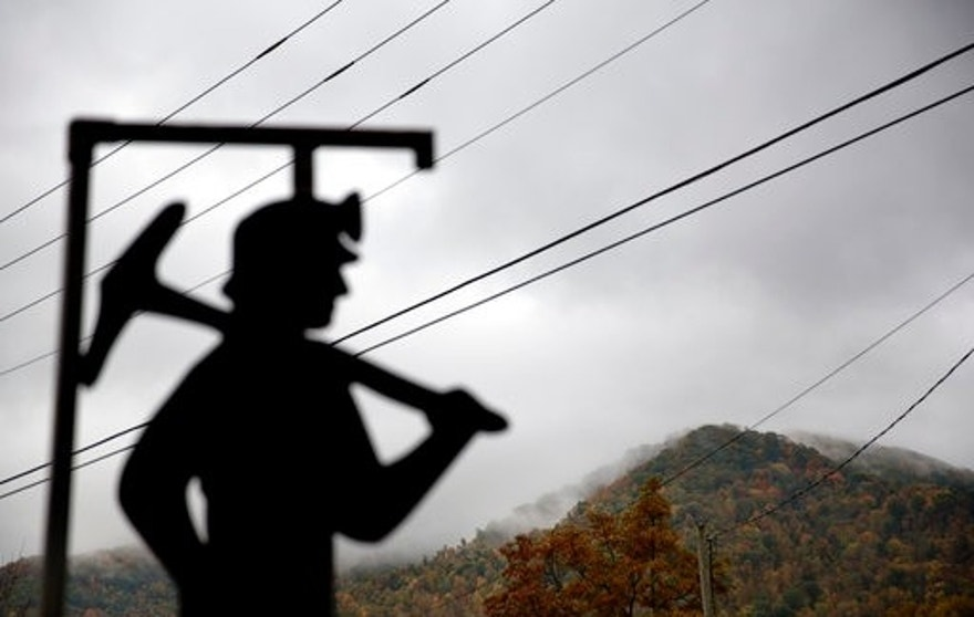 FILE - In this Oct. 16, 2014 file photo, fog hovers over a mountaintop as a cutout depicting a coal miner stands at a memorial to local miners killed on the job in Cumberland, Ky. The Republican-controlled Kentucky state legislature is on the cusp of lifting its decades-long moratorium on nuclear energy, a move unthinkable just three years ago in a state that has been culturally and economically dominated by coal. As the coal industry continues its slide, even Republican lawmakers are acknowledging a need for alternatives. (AP Photo/David Goldman, File)