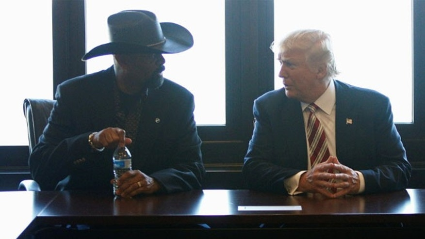 FILE: Then-candidate Donald Trump talks with Milwaukee County Sheriff David Clarke Jr.