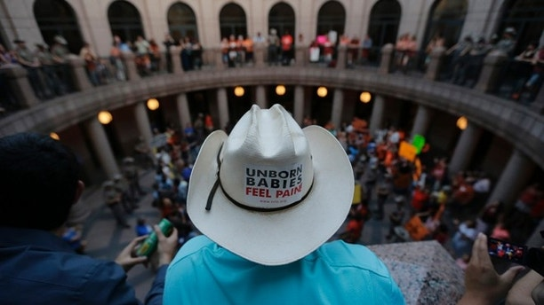 Opponents and supporters of an abortion bill gather in a courtyard outside a hearing for the bill at the state capitol, Tuesday, July 2, 2013, in Austin, Texas. Gov. Rick Perry has called lawmakers back for another special session with abortion on the top of the agenda. (AP Photo/Eric Gay)