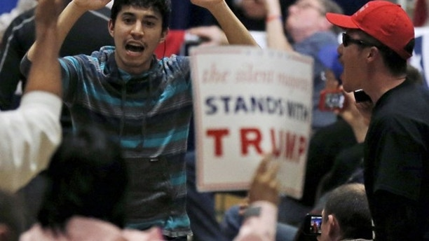 A protester (L) demonstrates during a U.S. Republican presidential candidate Donald Trump campaign rally in West Allis, Wisconsin, United States, April 3, 2016.     REUTERS/Jim Young  - RTSDEVW