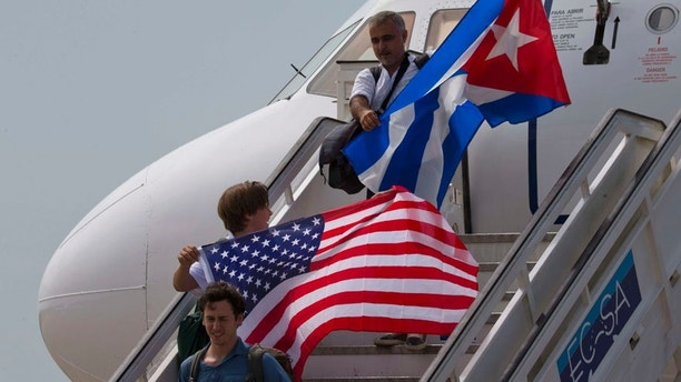 FILE- In this Aug. 31, 2016 file photo, two passengers deplane from JetBlue flight 387 waving a United States, and Cuban national flag, in Santa Clara. As President Donald Trump is expected to announce a reversal on the U.S. Cuba policy on Friday, June 16, 2017, Cubans are bracing for the worst. Across the island, people of all ages, professions and political beliefs expect rising tensions, fewer American visitors and a harder time seeing relatives in the U.S.(AP Photo/Ramon Espinosa, File)