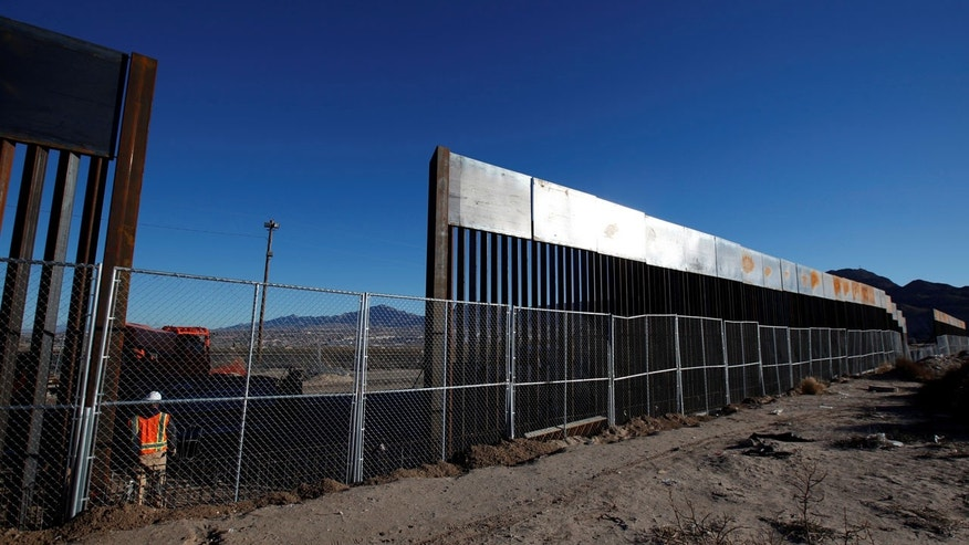 FILE: A worker stands next to a newly built section of the U.S.-Mexico border fence at Sunland Park, Calif.