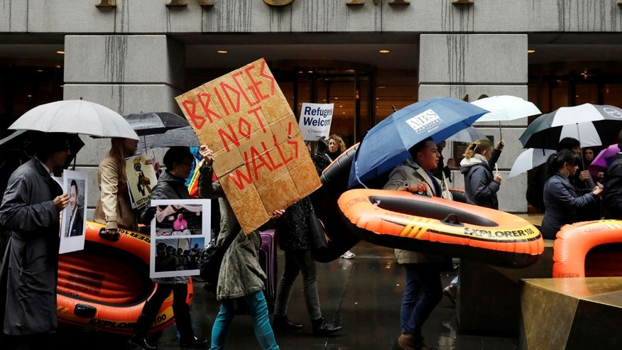 Demonstrators march outside the Trump Building at 40 Wall St. as part of a protest against the refugee ban in New York