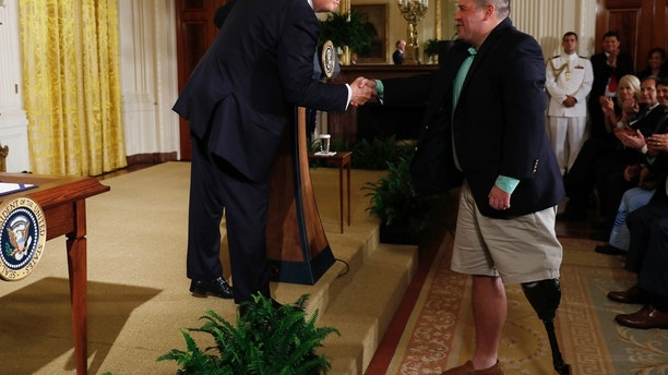 "U.S. President Donald Trump shakes hands with Sgt. Michael Verardo, who lost a leg in an IED explosion in Afghanistan, before signing the ""VA Accountability Act"" in the East Room of the White House in Washington, U.S., June 23, 2017. REUTERS/Jonathan Ernst - RTS18DN8"