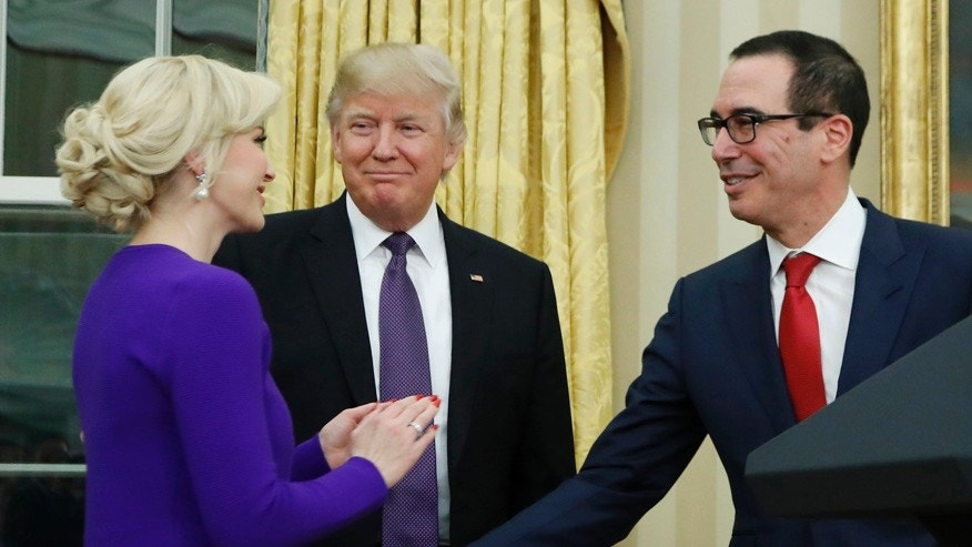 In this Feb. 13, 2017 file photo, President Donald Trump watches as Treasury Secretary Steven Mnuchin walks to his fiancée Scottish actress Louise Linton after he was sworn-in by Vice President Mike Pence, in the Oval Office of the White House in Washington.   Trump plans to be among the guests as Mnuchin weds Linton Saturday at the Andrew W. Mellon Auditorium in Washington.  (AP Photo/Manuel Balce Ceneta)