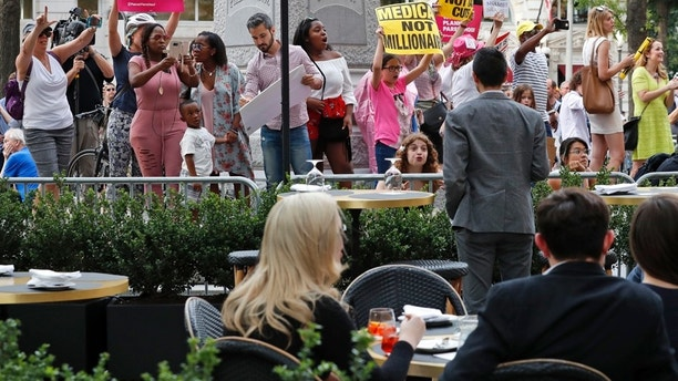 Protesters yell at patrons at the outdoor seating area at the Trump Hotel, Wednesday, June 28, 2017, in Washington. President Donald Trump is attending a fundraiser at the hotel. (AP Photo/Alex Brandon)