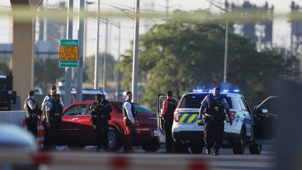 Chicago police work at the scene of a shooting that killed multiple people on the Chicago Skyway early Wednesday, June 21, 2017, in Chicago. The shooting prompted an early-morning closure of part of the expressway that connects the city with Indiana. (Alyssa Pointer/Chicago Tribune via AP)