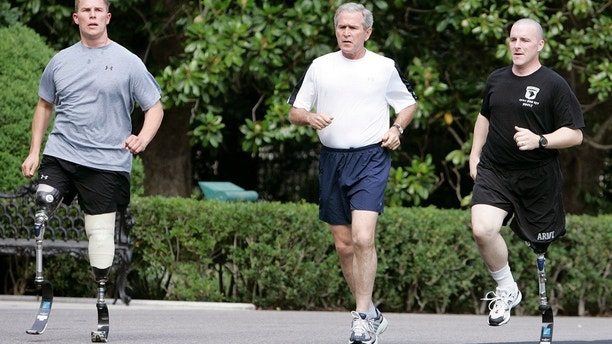 U.S. President George W. Bush (C) jogs with U.S. Army Sgt. Neil Duncan (L) and U.S. Army Specialist Max Ramsey at the White House in Washington July 25, 2007. Duncan lost both legs in Afghanistan in December 2005 and Ramsey lost his left leg in Iraq in March 2006.   REUTERS/Larry Downing   (UNITED STATES) - RTR1S8XP