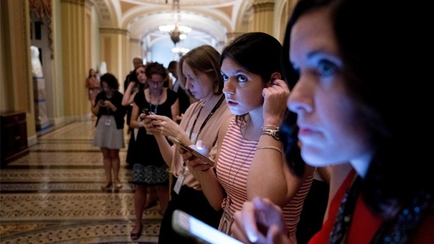 FILE: JUNE 22, 2017: Journalists outside a Senate Republican meeting on a health reform bill on Capitol Hill in Washington, D.C. (AP)