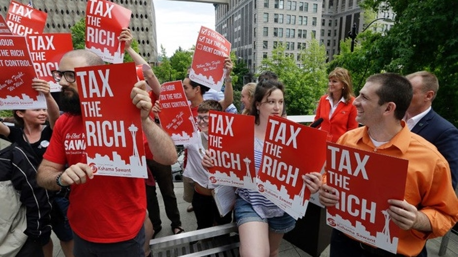 Demonstrators holding signs in favor of a new city income tax on the at a Seattle City Council Monday, July 10.